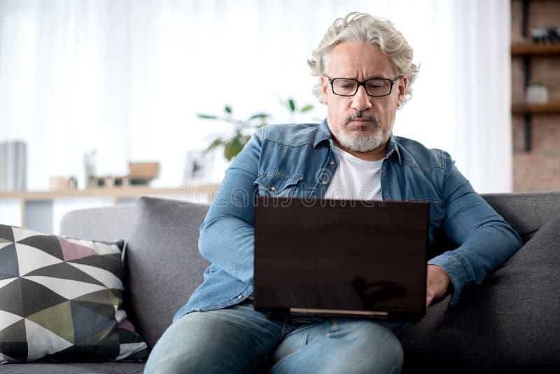 Homem idoso sério que datilografa no laptop fotos de stock