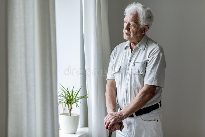 Homem idoso só com a vara de passeio que está pela janela alo imagem de stock