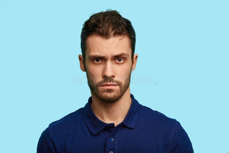 Homem incerto não barbeado cético considerável que veste o t-shirt azul que levantam no estúdio, a sua cara completamente da dúvi fotografia de stock royalty free