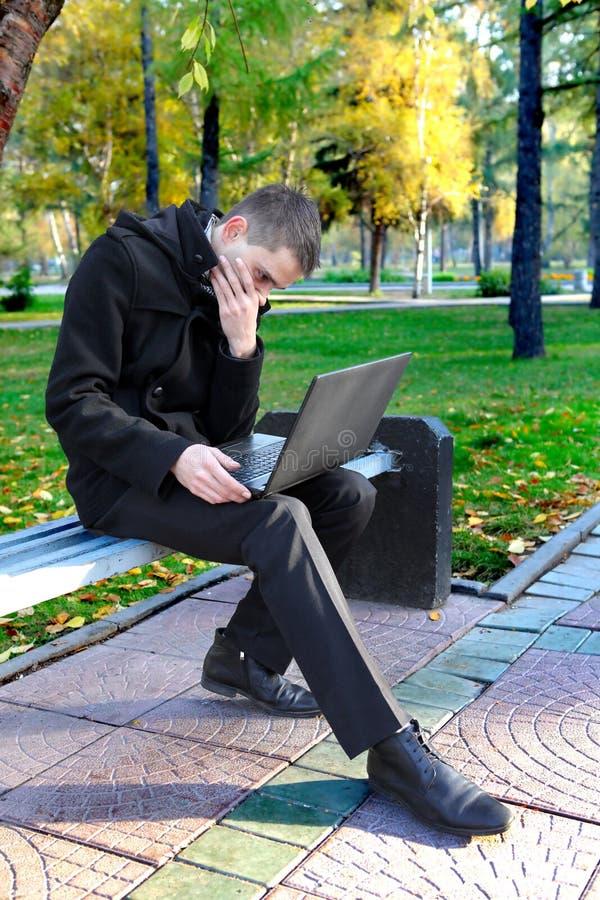 Homem com o portátil no parque imagens de stock