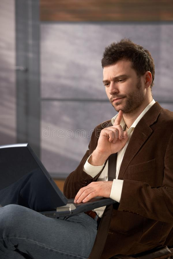 Homem incomodado com portátil imagem de stock royalty free