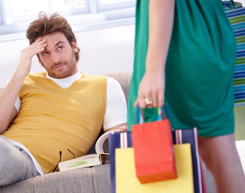 Homem incomodado e mulher shopaholic imagem de stock