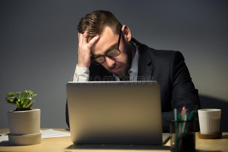 Homem incomodado que lê sobre o problema recente tarde na noite fotos de stock