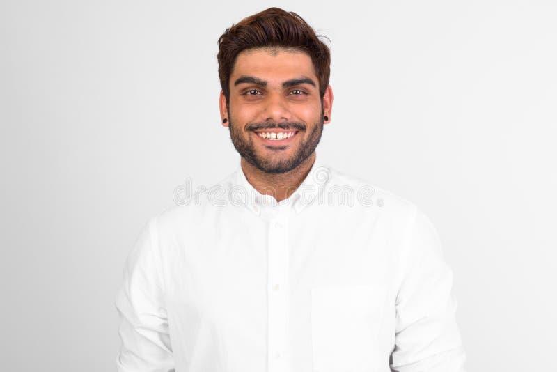 Homem indiano farpado novo feliz que sorri contra o fundo branco fotografia de stock royalty free