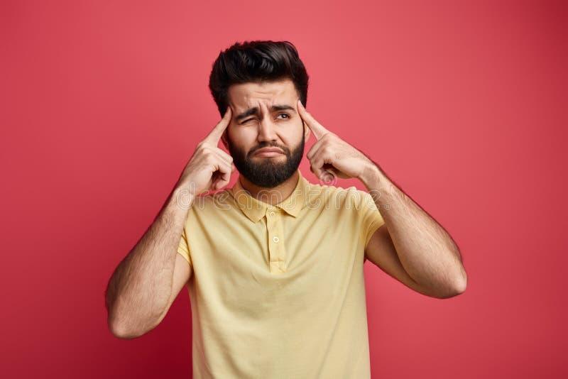 Homem indiano novo do thoughtfult pensativo triste que toca em templos com dedos imagens de stock