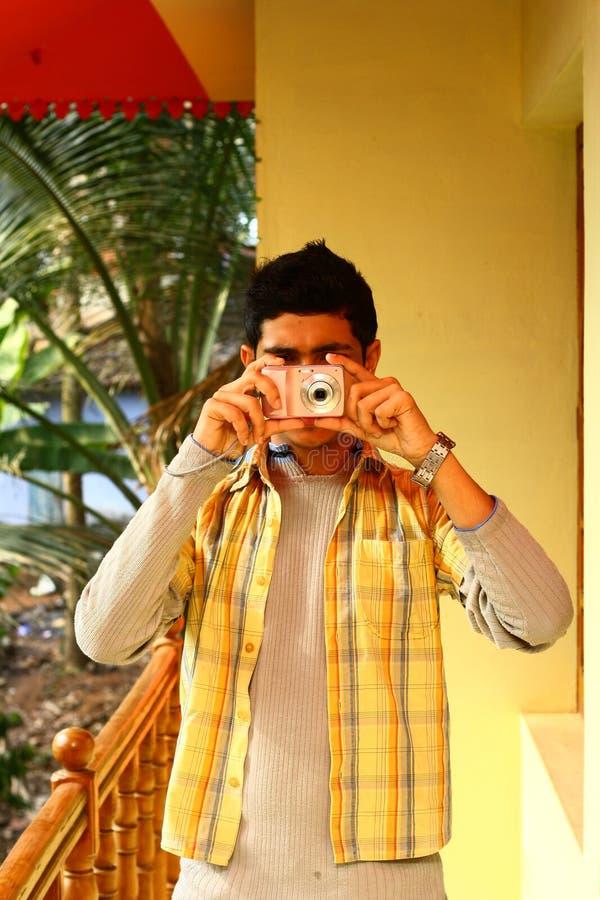 Homem indiano novo que toma a fotografia na câmera de P&S imagens de stock royalty free