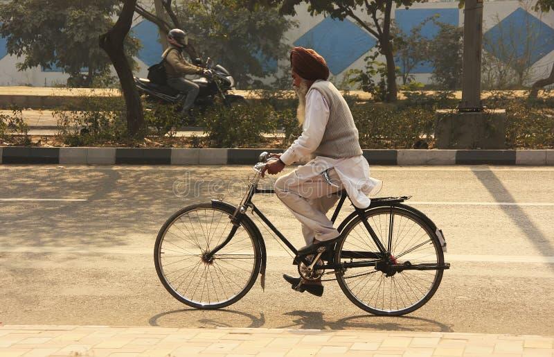Homem indiano que biking nas ruas de Nova Deli imagem de stock royalty free