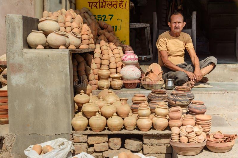 Homem indiano que vende potenciômetros de argila na oficina local em Bikaner Rajasthan India imagem de stock