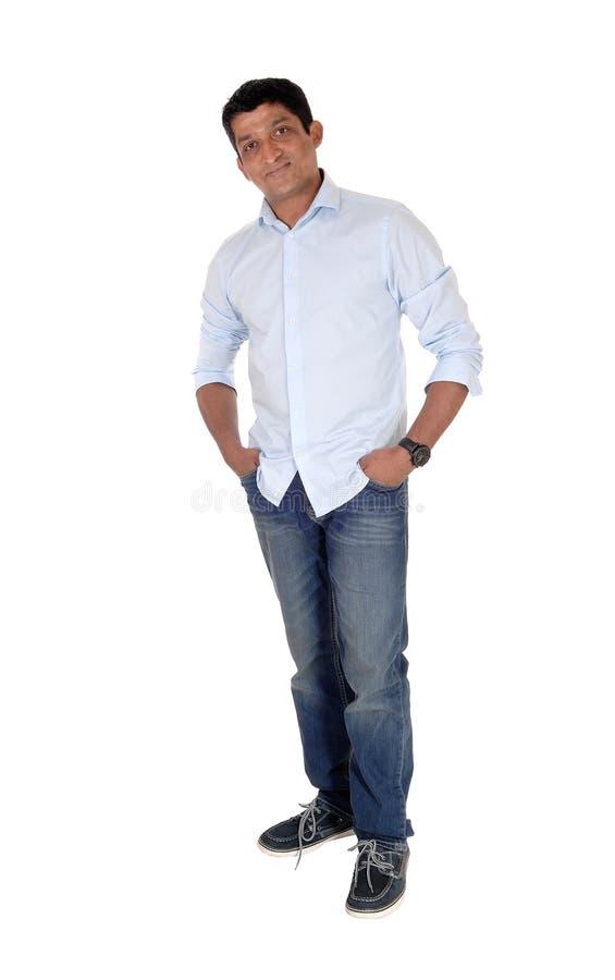 Homem indiano relaxado que está nas calças de brim e nas sapatilhas imagem de stock