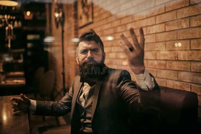 Homem indignante em um restaurante Homem de negócios com a barba longa no clube do charuto O cliente seguro da barra senta-se no  imagens de stock