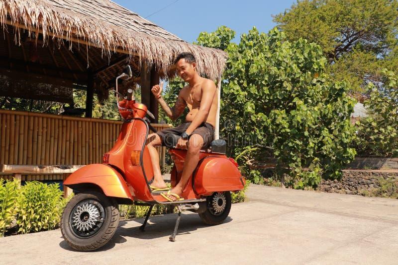 Homem indonésio que senta-se no 'trotinette' italiano tradicional Velomotor antiquado alaranjado, maneira tradicional indonésia d foto de stock