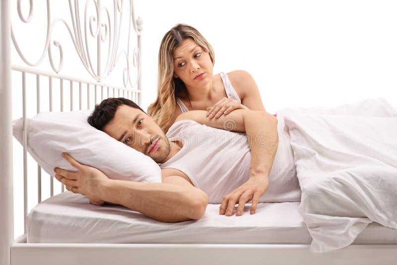 Homem infeliz que encontra-se na cama com a mulher interessada que consola o imagens de stock