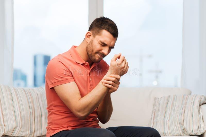 Homem infeliz que sofre da dor à disposição em casa foto de stock