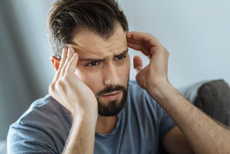 Homem infeliz triste que faz massagens seus templos imagem de stock