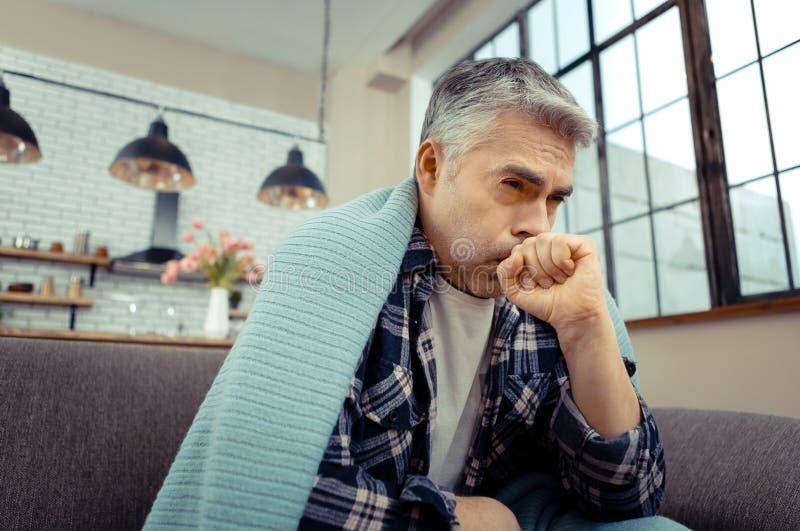 Homem infeliz triste que sofre da tosse forte fotografia de stock