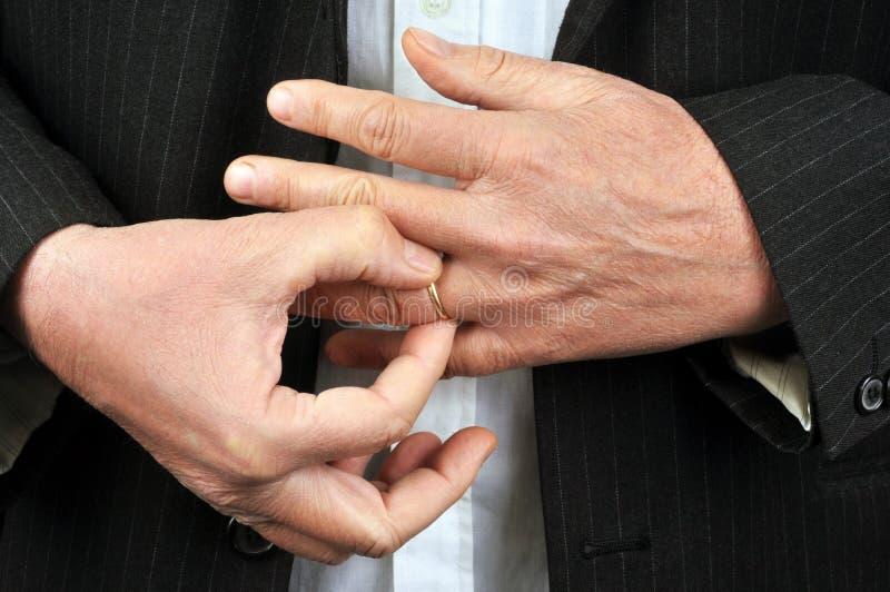 Homem infiel que retira sua aliança de casamento fotos de stock royalty free