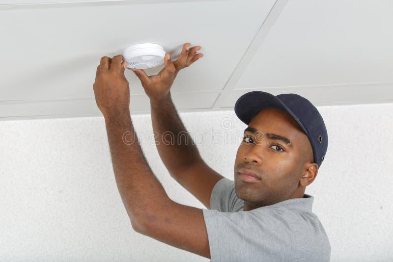 Homem inspecionando detector de fumaça foto de stock