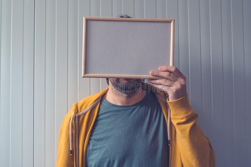 Homem irreconhecível que levanta com moldura para retrato vazia sobre sua cara imagens de stock