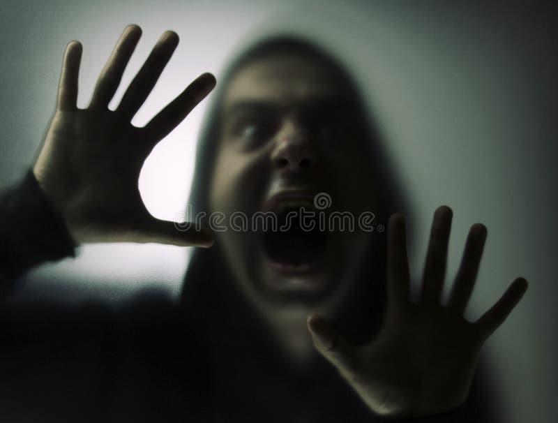 Homem irritado atrás do vidro imagem de stock