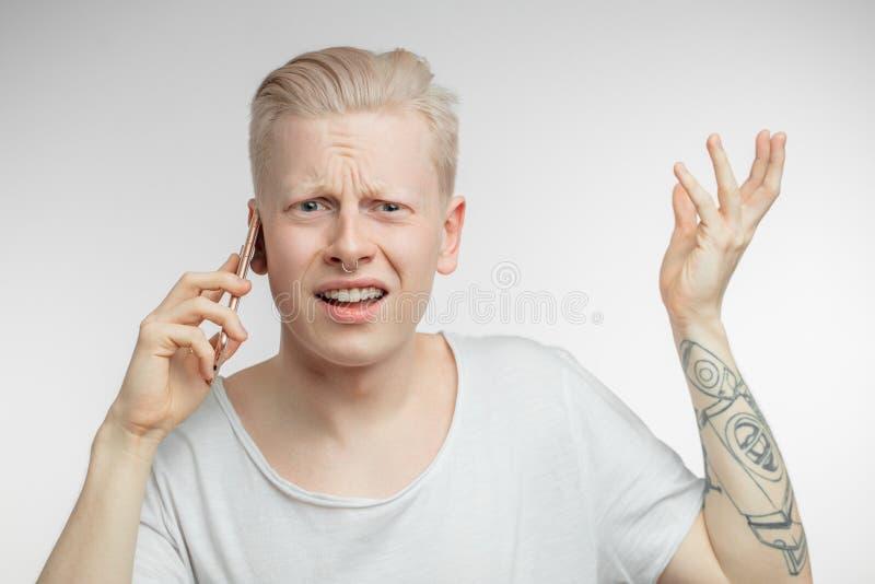 Homem irritado com a cara olhada de sobrancelhas franzidas que recebe a notícia desagradável no telefone celular imagem de stock royalty free