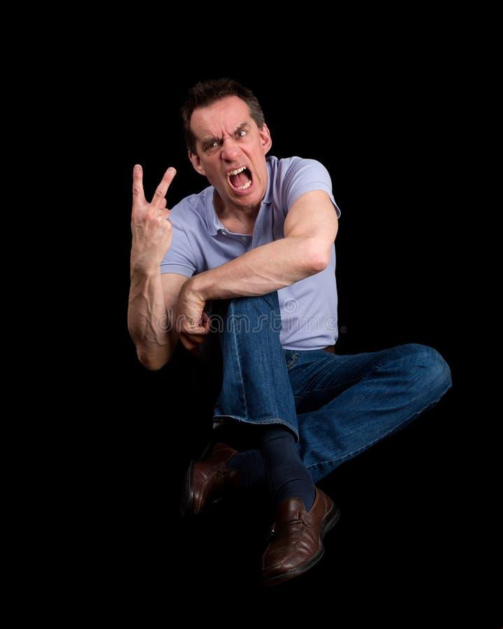 Homem irritado da gritaria que dá um gesto de dois dedos fotos de stock