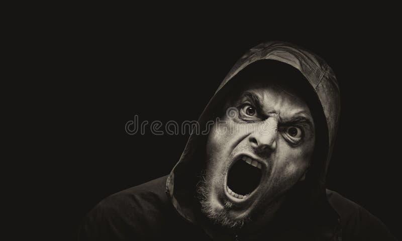 Homem irritado em um fundo escuro imagem de stock