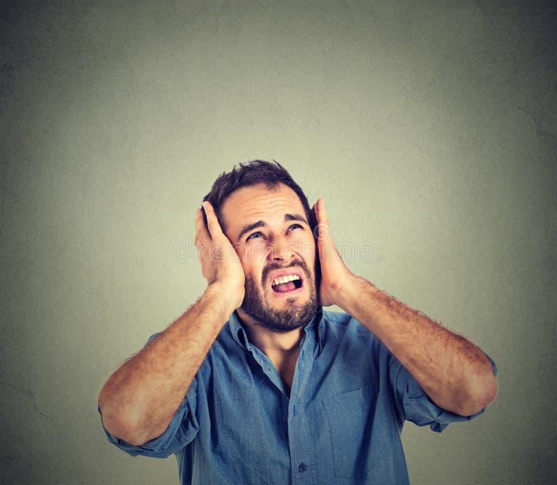 Homem irritado, forçado que cobre suas orelhas, olhando acima, parada que faz o ruído alto fotos de stock