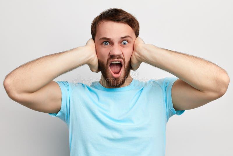 Homem irritado frustrante com as palmas em suas orelhas imagem de stock royalty free