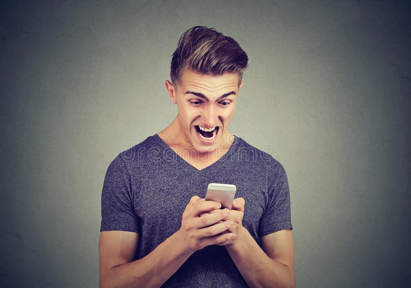 Homem irritado frustrante que lê uma mensagem de texto no smartphone que grita imagem de stock