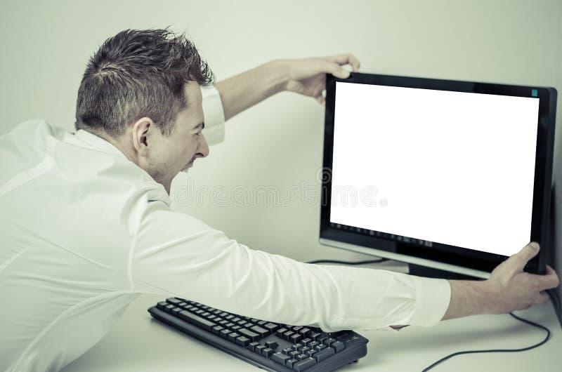 Homem irritado que agarra seu computador com uma tela branca fotografia de stock