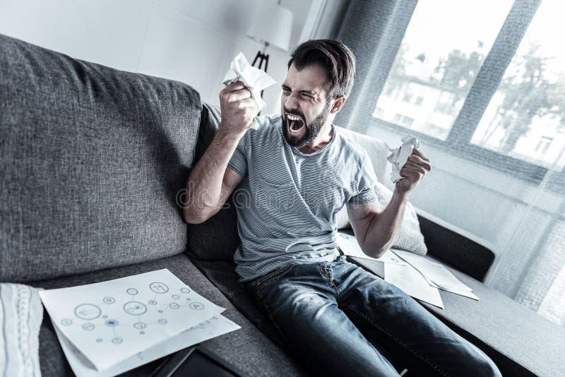 Homem irritado que amarrota documentos estragados foto de stock