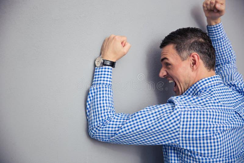 Homem irritado que bate a parede fotografia de stock royalty free