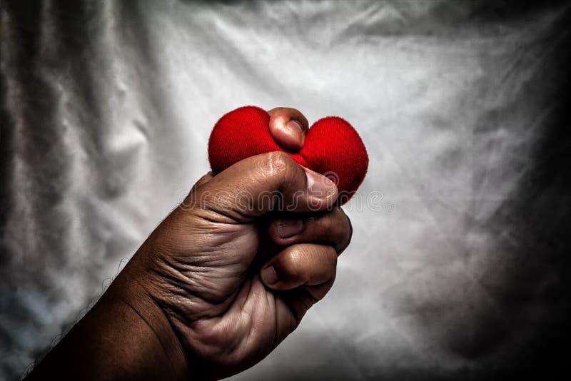 homem irritado que esmaga o coração vermelho à disposição , amor não recompensado , amor co fotografia de stock royalty free