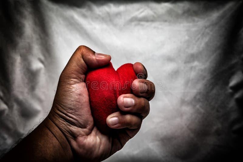 homem irritado que esmaga o coração vermelho à disposição , amor não recompensado , amor co fotos de stock