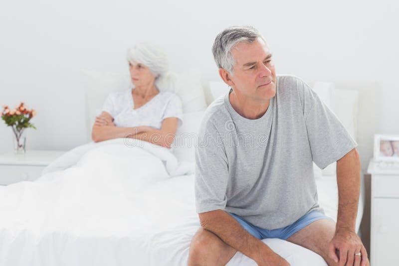 Homem irritado que senta-se na cama durante uma disputa foto de stock royalty free