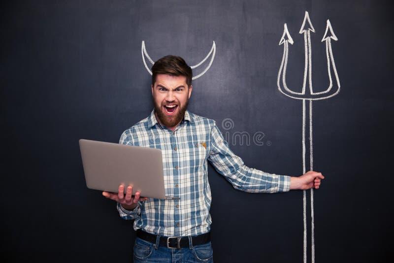 Homem irritado que usa o portátil e mantendo o tridente tirado no quadro-negro fotografia de stock