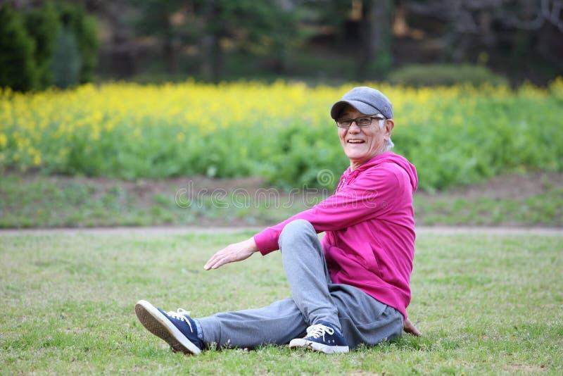 Homem japon?s superior que veste o Parka cor-de-rosa que faz o estiramento assentado da tor??o do torso em um gramado foto de stock