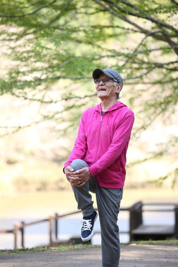 Homem japon?s superior que veste o Parka cor-de-rosa que faz o joelho estando ao estiramento da caixa imagens de stock royalty free