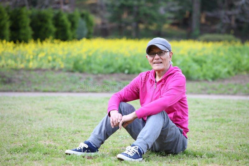 Homem japon?s superior que veste o Parka cor-de-rosa que senta-se em um gramado imagens de stock