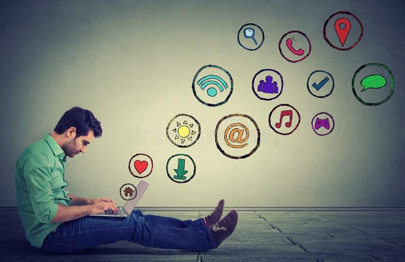 Homem lateral do perfil que trabalha no portátil usando a aplicação social dos meios que senta-se em um assoalho imagem de stock royalty free