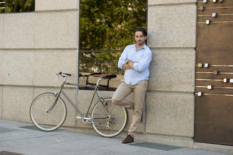 Homem latin atrativo feliz na equitação alegre de sorriso da roupa na moda ocasional na bicicleta retro fresca do vintage foto de stock