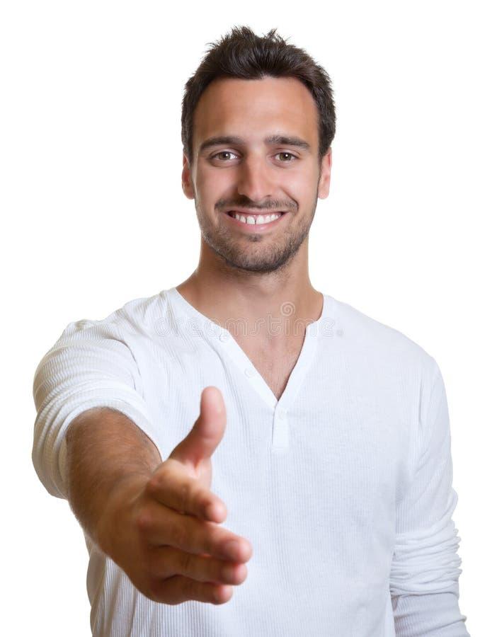 Homem latin novo que dá a mão fotografia de stock royalty free
