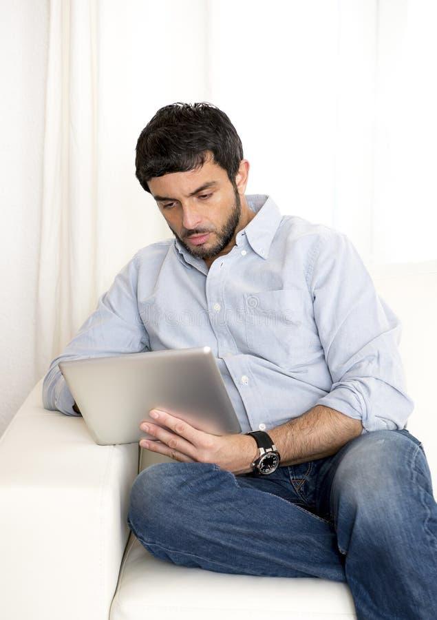 Homem latino-americano atrativo novo em casa no sofá branco usando a tabuleta ou a almofada digital fotografia de stock royalty free