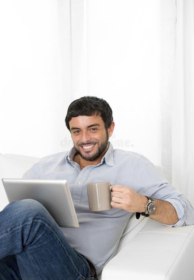 Homem latino-americano atrativo novo em casa no sofá branco usando a tabuleta ou a almofada digital foto de stock