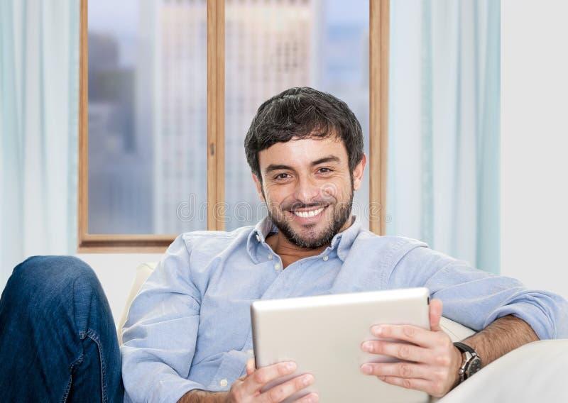 Homem latino-americano atrativo novo em casa que senta-se no sofá branco usando a tabuleta digital fotografia de stock royalty free