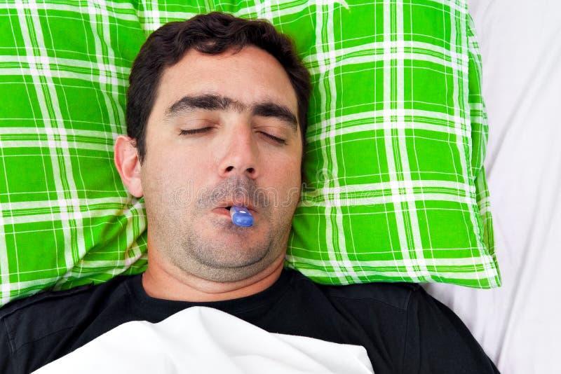 Homem latino-americano doente que coloca na cama com um termômetro imagens de stock royalty free