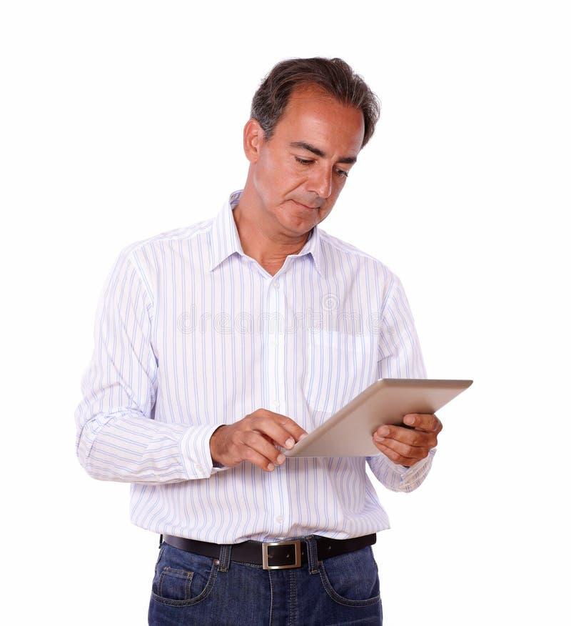 Homem latino-americano maduro que usa seu PC da tabuleta foto de stock royalty free