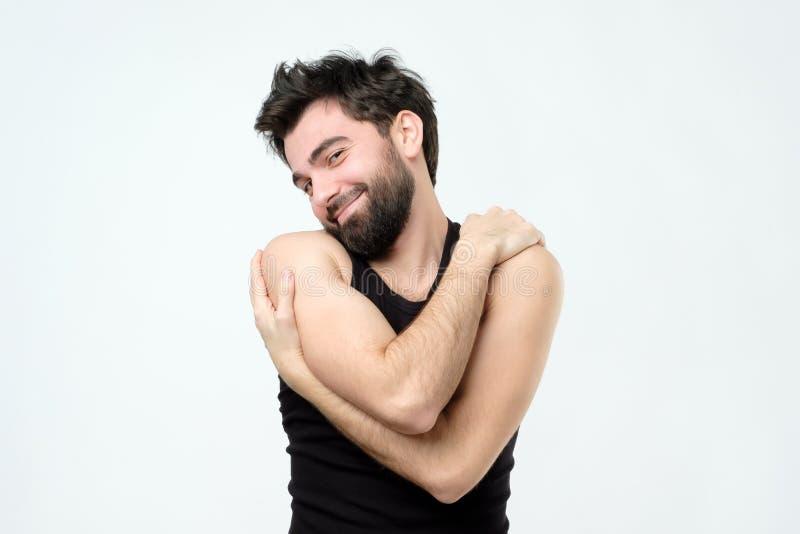 Homem latino-americano novo considerável alegre que sorri com prazer ao abraçar-se foto de stock