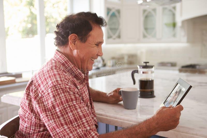 Homem latino-americano superior em casa que olha a fotografia velha foto de stock royalty free