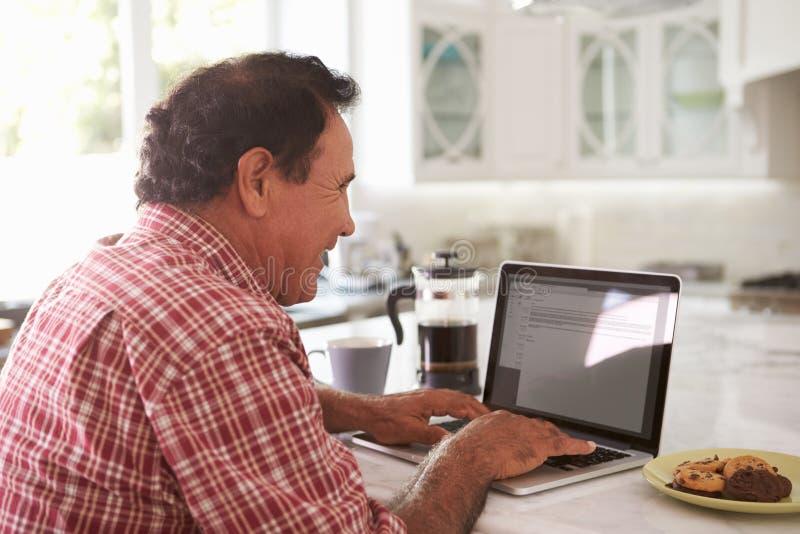 Homem latino-americano superior que senta-se em casa usando o portátil fotos de stock